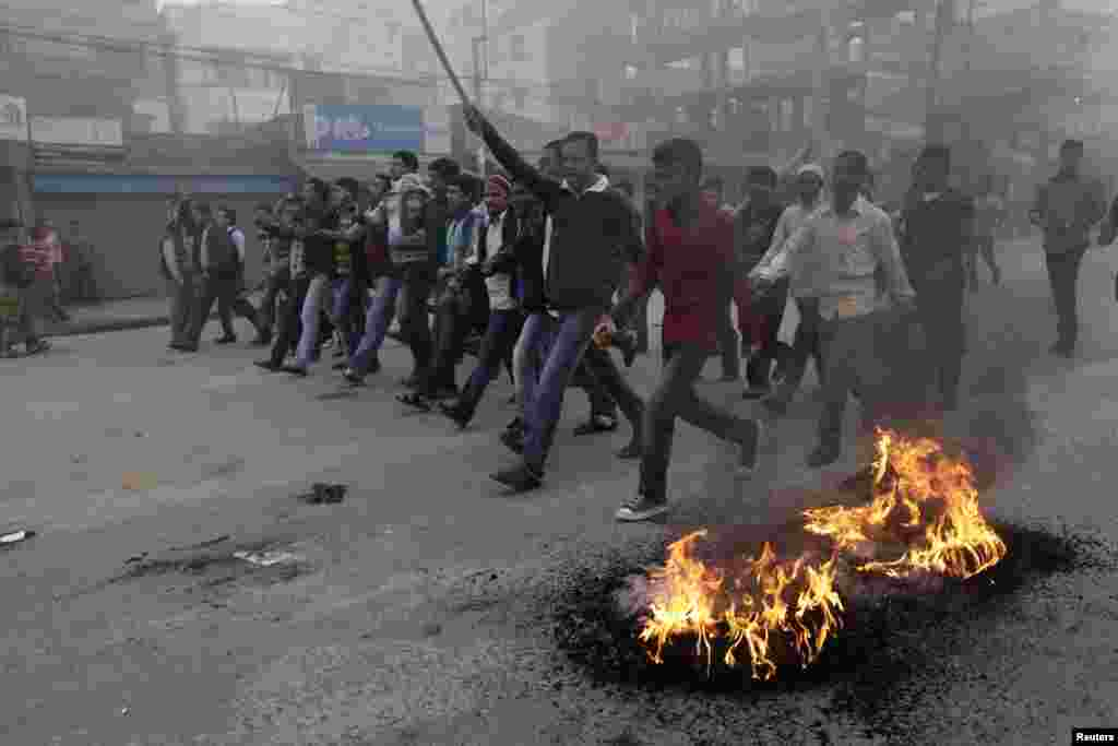 Activists of the Bangladesh Nationalist Party (BNP) shout slogans as they set fire to tyres during a nationwide blockade in Dhaka December 9, 2012. Police fired rubber bullets and tear gas to disperse protesters staging blockades across Bangladesh on Sund