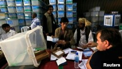 Petugas pemilu Afghanistan menghtiung kartu-kartu suara dalam audit pilpres di Kabul (27/8).