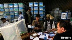 Afghan election workers count ballot papers for an audit of the presidential run-off, in Kabul, Afghanistan, Aug. 27, 2014.