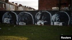 FILE - A mural of the Beatles is seen painted on the end of a row of terraced houses in Liverpool, northern England, Feb. 18, 2015.