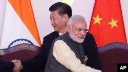 资料照片:参加在印度举行的金砖峰会的中、印领导人与其他成员国领导人握手。(2016年10月16日)