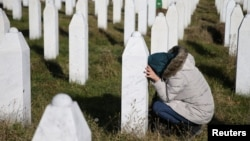 FILE - A woman visits a grave of her family members in the memorial center Potocari near Srebrenica, Bosnia and Herzegovina, after the court proceedings of former Bosnian Serb general Ratko Mladic, Nov. 22, 2017.
