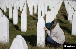 FILE - A woman visits a grave of one of her family members in the memorial center Potocari near Srebrenica, Bosnia and Herzegovina, after the court proceedings of former Bosnian Serb general Ratko Mladic, Nov. 22, 2017.