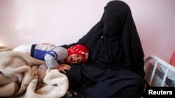 A child cries as he lays on the lap of his mother at a cholera treatment center in Sana'a, Yemen, Oct. 29, 2016.