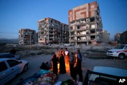In this photo provided by the Iranian Students News Agency, ISNA, survivors of the earthquake warm themselves in front of destroyed buildings at the city of Sarpol-e-Zahab in western Iran, Monday, Nov. 13, 2017.