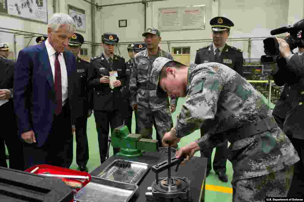 Secretary of Defense Chuck Hagel is given a tour by a Chinese military officer at the Non-Commissioned Officer Academy in Beijing, China April 9, 2014. (Department of Defense)