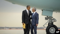 President Barack Obama is greeted by Chicago Mayor Rahm Emanuel upon his arrival on Air Force One at O'Hare International Airport in Chicago, Oct. 25, 2012.