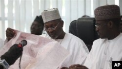 Attahiru Jega, Independent National Electoral Commission Chairman, reads the results sheet before he declared Nigeria's incumbent President Goodluck Jonathan as the winner of last Saturday's presidential election.
