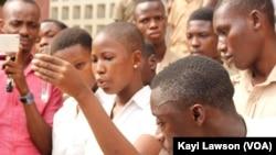 Une élève entourée de ses condisciples fait une expérience de chimie au Lycée d'Adamavo, Lomé, 12 janvier 2018. (VOA/Kayi Lawson)