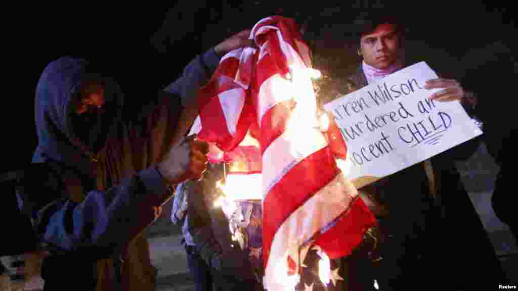 A protester burns an American flag on Highway 580 during a demonstration following the grand jury decision in the Ferguson, Missouri shooting of Michael Brown, in Oakland, California, November 24, 2014.
