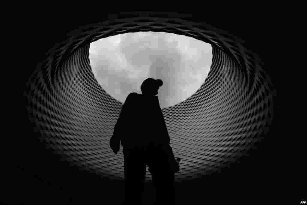 មនុស្សម្នាក់ដើរពីក្រោមដំបូលនៃសាលពិព័រណ៍ដែលរចនាដោយក្រុមហ៊ុន Herzog & de Meuron របស់ស្វ៊ីស ក្នុងថ្ងៃបើកជាសាធារណៈជាផ្លូវការរបស់អង្គការ Art Basel។