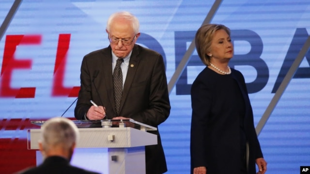 Democratic presidential candidate, Hillary Clinton enters the stage after a break as Democratic presidential candidate, Sen. Bernie Sanders, I-Vt,  makes notes, March 9, 2016.