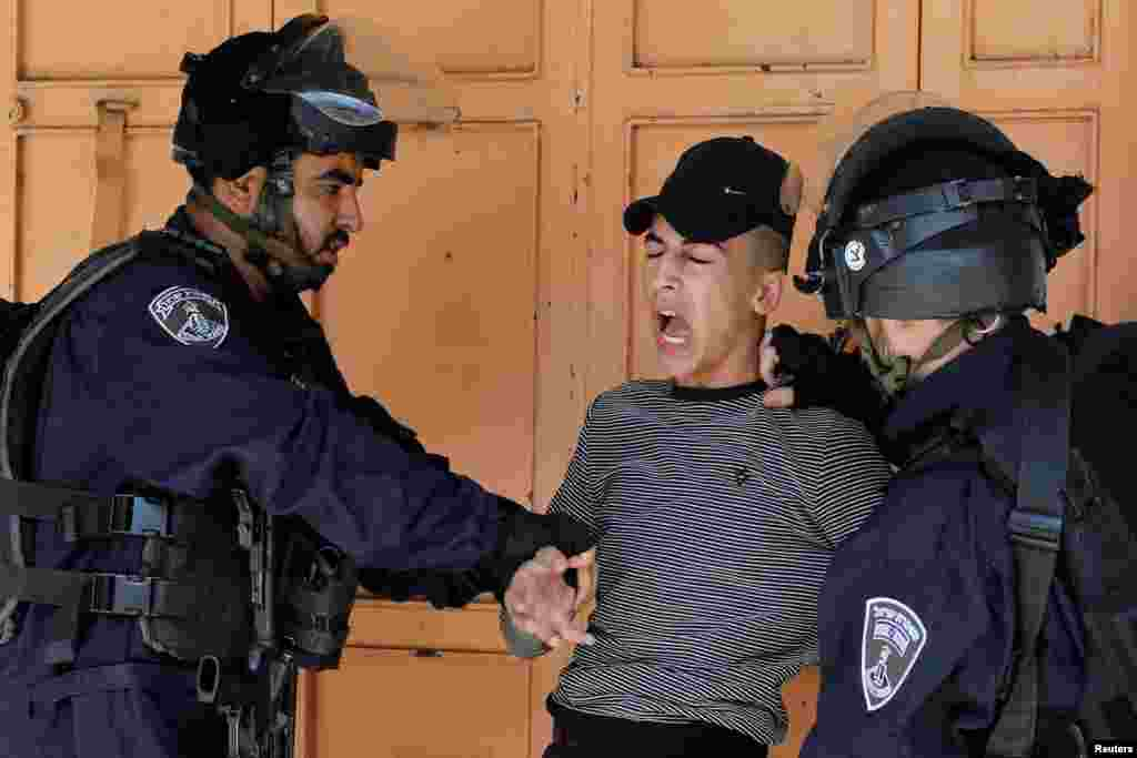 Israeli border police members detain a Palestinian during a protest against Israel's plan to annex parts of the occupied West Bank, in Heron.