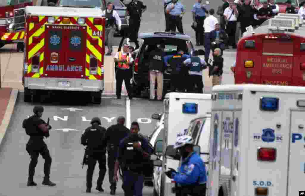 Emergency vehicles and law enforcement personnel respond to a shooting at an entrance to the Washington Navy Yard, Sept. 16, 2013.