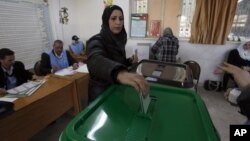 A woman casts her vote at a polling station during the first hours of the Jordanian Parliamentary elections, in Al-Salt, Jordan, January 23, 2013.