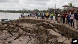 남미 페루 유리마구아스 외곽에 규모 8.0의 강한 지진이 발생한 후 시민들이 무너진 우아야가 강둑 옆을 걷고 있다.