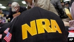 FILE- Illinois gun owners and supporters fill out National Rifle Association applications in Springfield, Ill., March 7, 2012. The 19-year-old authorities say killed 17 people at a Florida high school excelled in an air-rifle marksmanship program supported by a grant from the National Rifle Association Foundation, part of a multimillion-dollar effort by the gun group to support youth shooting clubs.