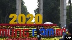 ໃນວັນທີ 30 ທັນວາ 2019 ເພື່ອຕ້ອນຮັບປີໃໝ່ 2020 ປະຊາຊົນໃນນະຄອນຫລວງຮາໂນ່ຍ ຄົນນຶ່ງເອົາດອກໄມ້ມາປະດັບໜ້າບ້ານ (ພາບຖ່າຍໂດຍ Nhac NGUYEN ຈາກອົງການຂ່າວ AFP)