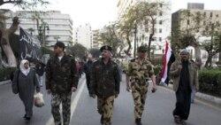 وسط یک مقام نظامی ارتش، به همراه چند سرباز بیرون از ساختمان پارلمان مصر در قاهره راه می رود - ۹ فوریه ۲۰۱۱