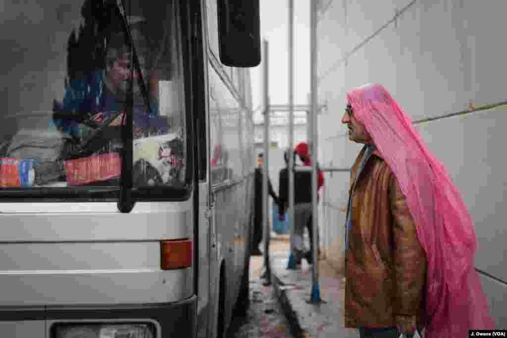 Seorang pria siap naik bus yang akan meninggalkan Kamp Vial di Chios.