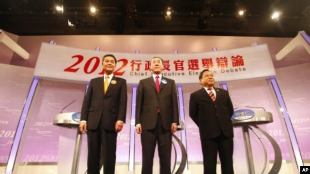 Hong Kong Chief Executive candidates (L-R) Leung Chun-ying, Henry Tang and Albert Ho stand on the stage after a live television debate in Hong Kong, March 16, 2012.