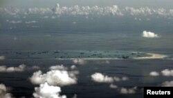 Bức ảnh trên không qua cửa kính của một máy bay quân sự Philippines cho thấy cáo buộc Trung Quốc đang khai hoang đất tại bãi đá ngầm ở quần đảo Trường Sa, Biển Đông, phía tây Palawan, Philippines.