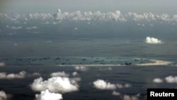 FILE - An aerial photo taken though a glass window of a Philippine military plane shows the alleged ongoing land reclamation by China on mischief reef in the Spratly Islands in the South China Sea, west of Palawan, Philippines.