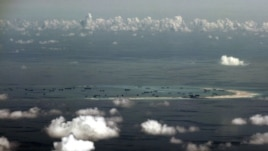 An aerial photo taken though a glass window of a Philippine military plane shows the alleged ongoing land reclamation by China on mischief reef in the Spratly Islands in the South China Sea, west of Palawan, Philippines.