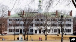 FILE - Students walk across the Dartmouth College campus green in Hanover, N.H., March 12, 2012.