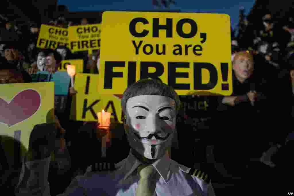 대한항공 직원들이 촛불 집회를 열어 한진그룹 총수 조양호 회장 일가의 갑질을 규탄하는 가운데, 직원들이 회사 측의 색출을 막기 위해 가면을 쓰고 있다.