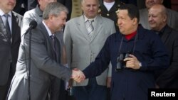 Venezuela's President Hugo Chavez (R) and First Deputy Prime Minister of Belarus Vladimir Semashko shake hands after their meeting at Miraflores Palace in Caracas, Venezuela, June 2, 2012.