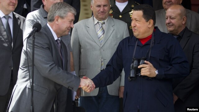 Venezuela's President Hugo Chavez (R) and First Deputy Prime Minister of Belarus Vladimir Semashko shake hands after their meeting at Miraflores Palace in Caracas, Venezuela, June 2, 2012.