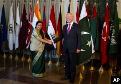 FILE - Indian Foreign Minister Sushma Swaraj (L) shakes hand with Pakistan's top adviser for foreign affairs, Sartaj Aziz, prior to their meeting in Islamabad, Pakistan, Dec. 9, 2015.