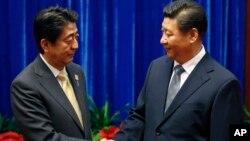 日本首相安倍晉三(左)和中國國家主席習近平(右)在亞太經合組織舉行期間在人民大會堂握手。