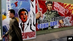 """一名朝鮮人2013年3月26日在朝鮮平壤走過巨大的宣傳海報,上面寫著威脅懲罰""""美帝國主義者和他們盟友"""" 的標語"""