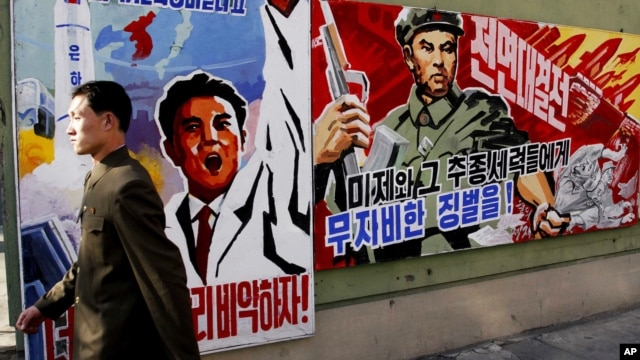 "A North Korean man walks past propaganda posters in Pyongyang, North Korea, that threatens punishment to the ""U.S. imperialists and their allies,"" March 26, 2013."