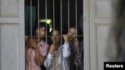 缅甸农民在一个寺庙中望着警察,抗议一个铜矿占用26个村庄的土地