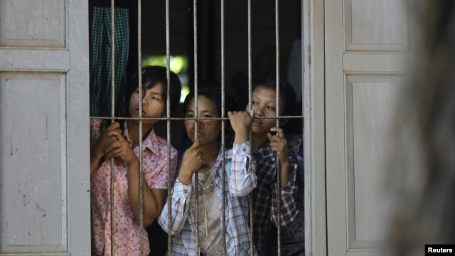 Burmese farmers look at police from inside a monastery in protest against the seizing of farmland across 26 villages for a copper mine project in Sarlingyi Township, September 12, 2012.