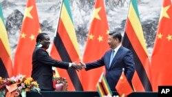 Perezida wa Zimbabwe, Emmerson Mnangagwa, ibubamfu, aramukanya na mugenzi we w'Ubushinwa Xi Jinping inyuma yo gusinya amasezerano mu vyo gufashanya, Beijing, China, itariki 3/04/2018.