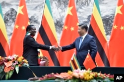 FILE - Zimbabwean President Emmerson Mnangagwa, left, shakes hands with Chinese President Xi Jinping as they pose for the media after a signing ceremony at the Great Hall of the People in Beijing, China, April 3, 2018.