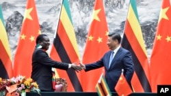 Zimbabwean President Emmerson Mnangagwa, left, shakes hands with Chinese President Xi Jinping as they pose for the media after a signing ceremony at the Great Hall of the People in Beijing, China, April 3, 2018.
