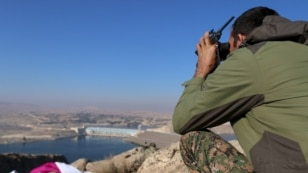 FILE - A fighter from the Syrian Democratic Forces takes a position atop Mount Annan overlooking the Tishrin Dam, after they captured it from Islamic State militants, south of Kobani, Syria, Dec. 27, 2015.
