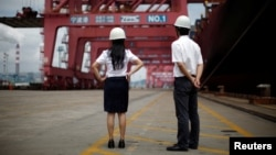 FILE - Employees stand next to a container ship at Ningbo port in Ningbo, Zhejiang province, June 21, 2012.