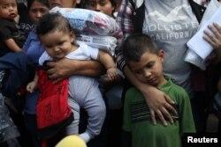 텍사스주 매캘런의 한 수용시설에서 풀려난 불법 이민자 가족들이 버스터미널에서 줄지어 서 있다.