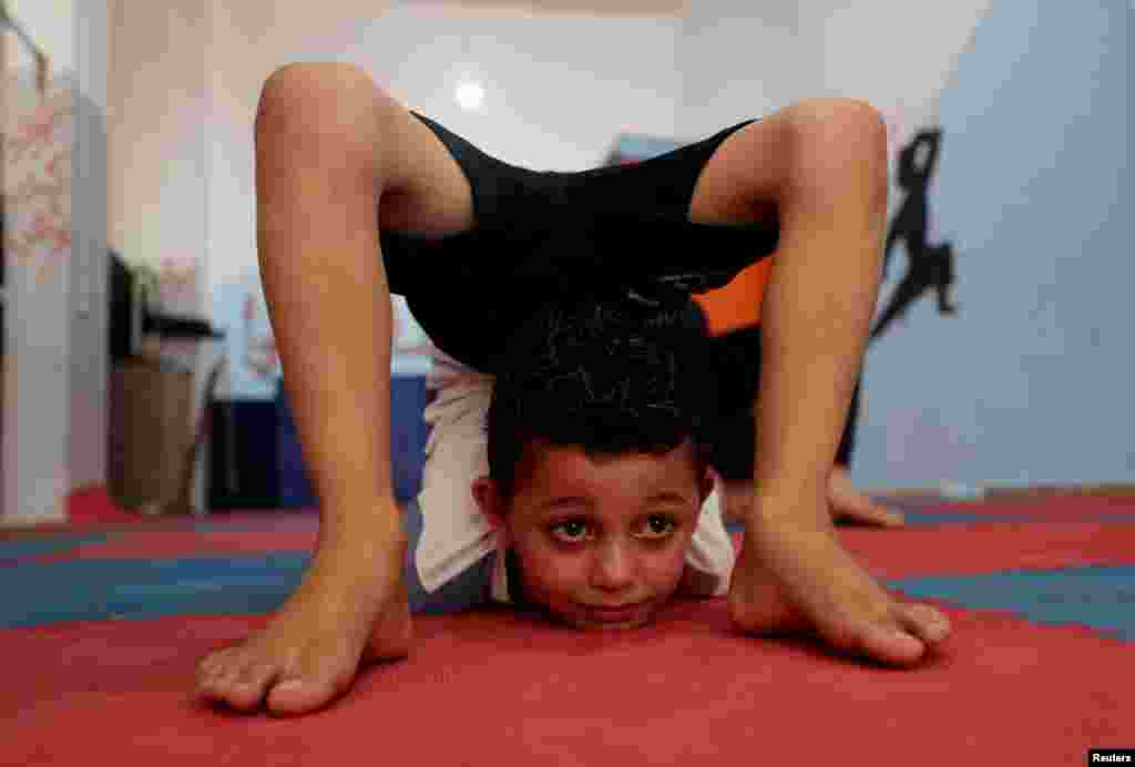 A Palestinian boy performs during a yoga and flexibility class on International Yoga Day in a club in Gaza City.