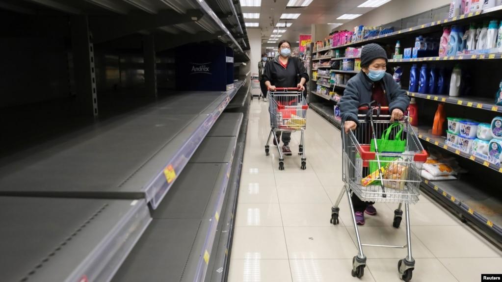 Khách hàng mang khẩu trang đi ngang qua một kệ giấy vệ sinh trống rỗng tại một siêu thị Hong Kong, ngày 6/2/2020