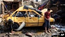 2月8日一名男孩站在一部受到炸彈襲擊毀壞不堪的汽車旁。