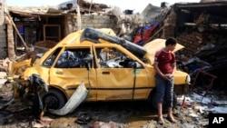 Irački dečak stoji kraj automobila uništenog u današnjem bombaškom napadu u bagdadskoj četvrti Kazimja