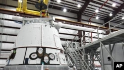 The SpaceX Dragon capsule is lifted to be placed atop its cargo ring inside a processing hangar at Cape Canaveral Air Force Station in Florida.