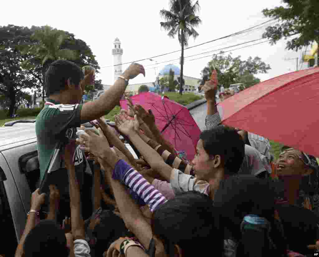 A Philippine Muslim hands out cash to children following prayers at the Blue Mosque (background) in Taguig city, east of Manila, Philippines, October 26, 2012.